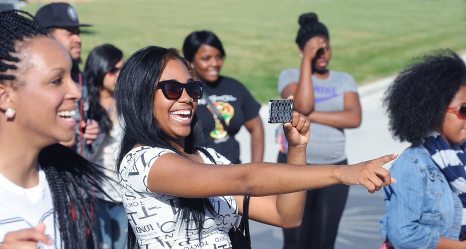 Student smiles for selfie during DPAS annual new student reception and cookout.