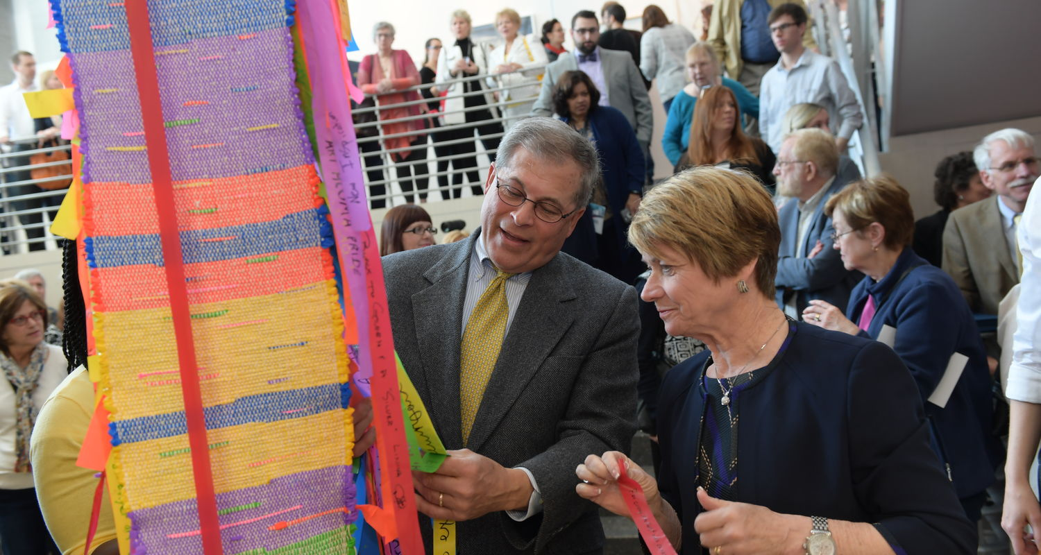 President Warren (right) and trustees chair Dennis Eckart (left) add to collaborative project at CVA opening