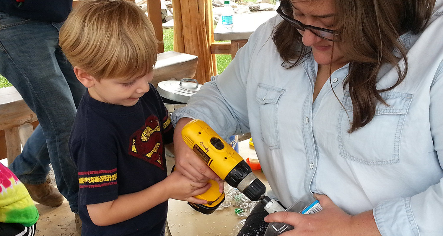 A child helps to construct an eco-friendly playhouse outside Kent State University's Child Development Center.