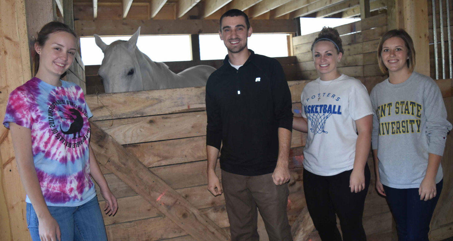 Kent State East Liverpool students in the occupational therapy assistant program participate in their pediatric clinical experience at Focus Hippotherapy. From left are Andreea Lang, Matt McLaughlin, Taylar Jordan and Alycia Nicholson – with Kobe.