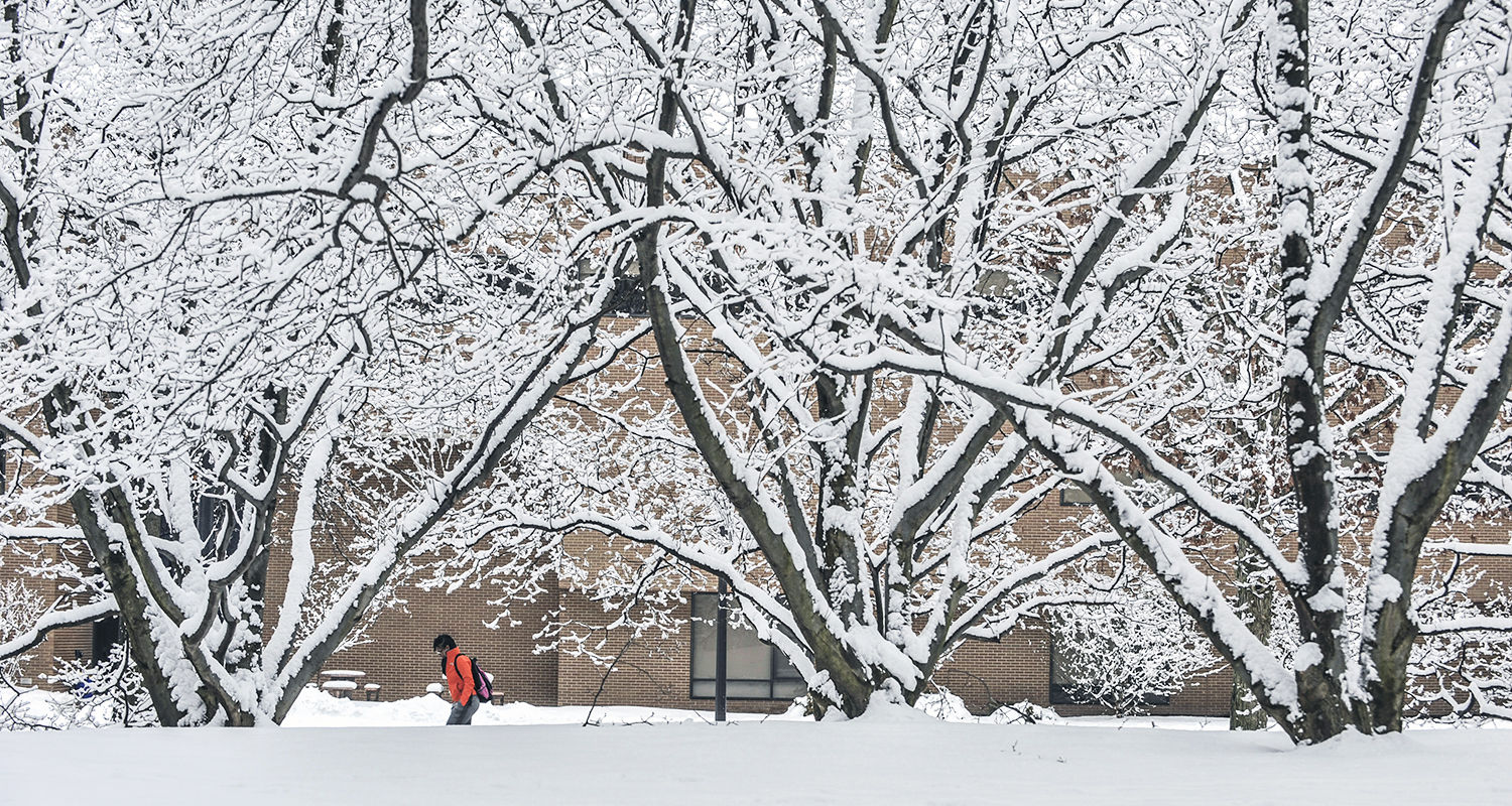A student walks to class on a snowy day at the Kent Campus.