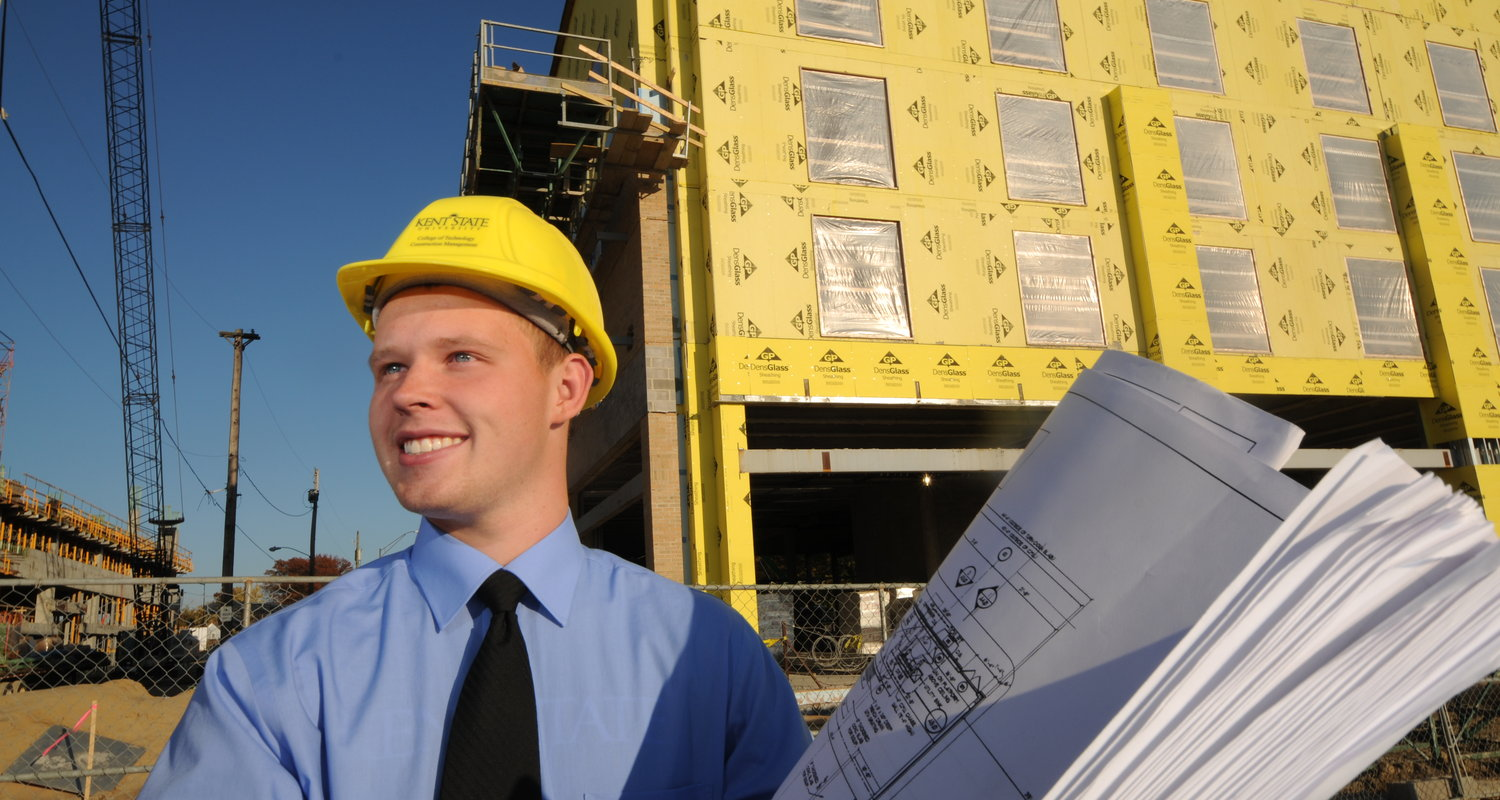 A CAEST student holding blueprints