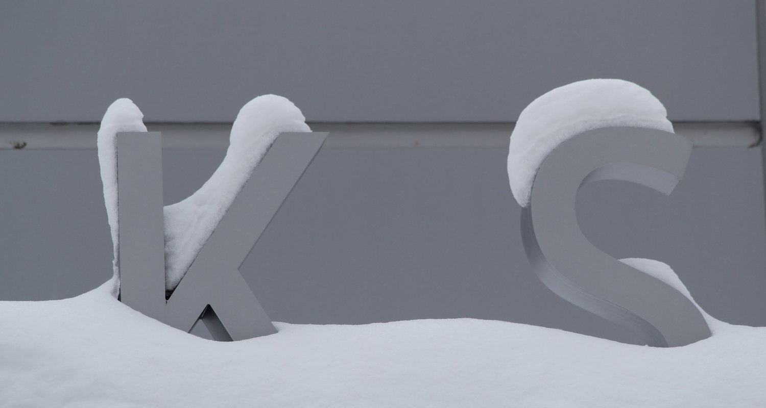 Snow covered letters K and S on an Ashtabula campus building