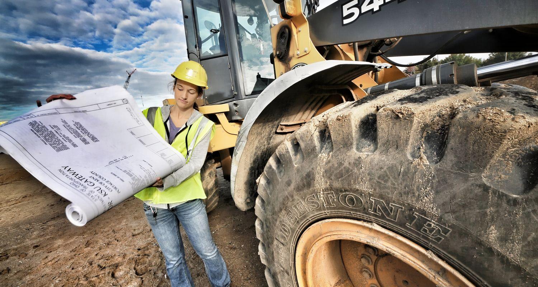 Construction management student on-site reading blueprints