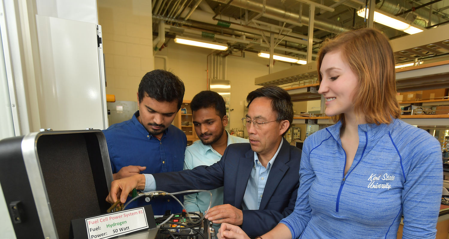 Angela Deibel inspects a fuel cell system with mentor Yanhai Du and two grad student colleagues