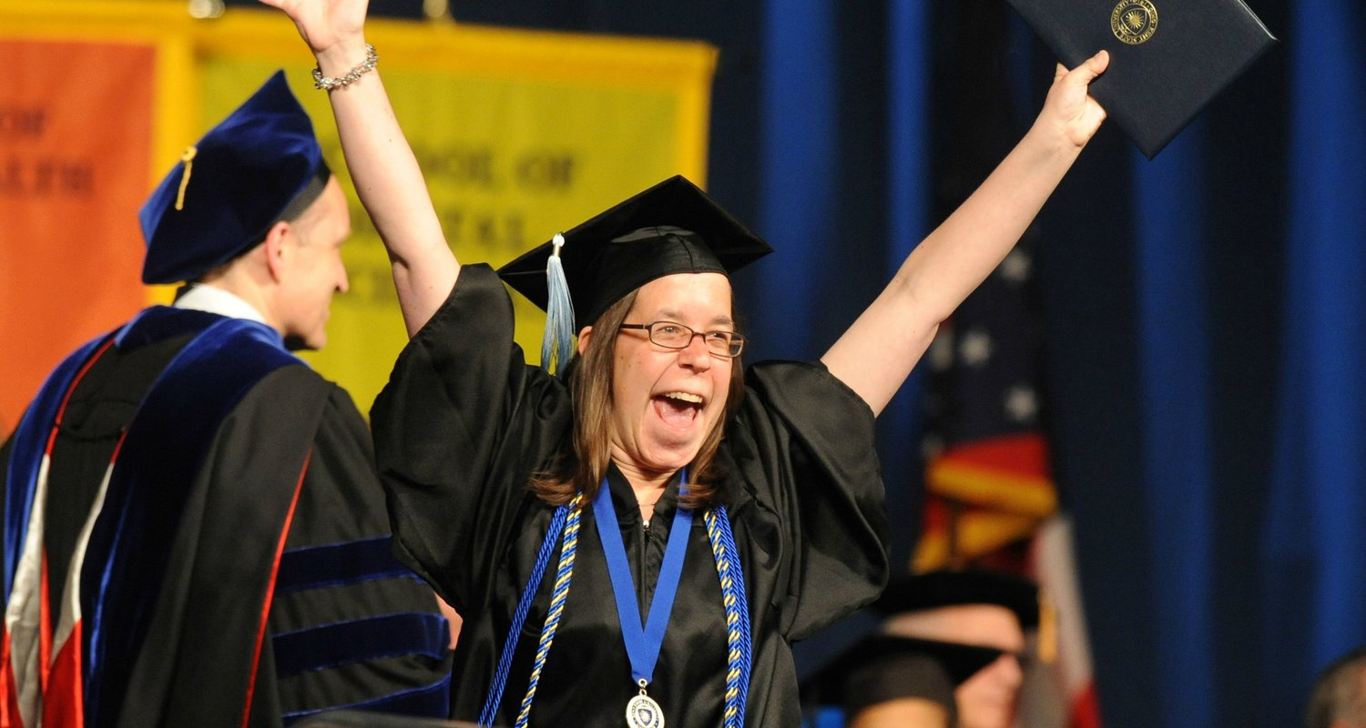 An Honors student expresses her excitement with arms up at graduation.