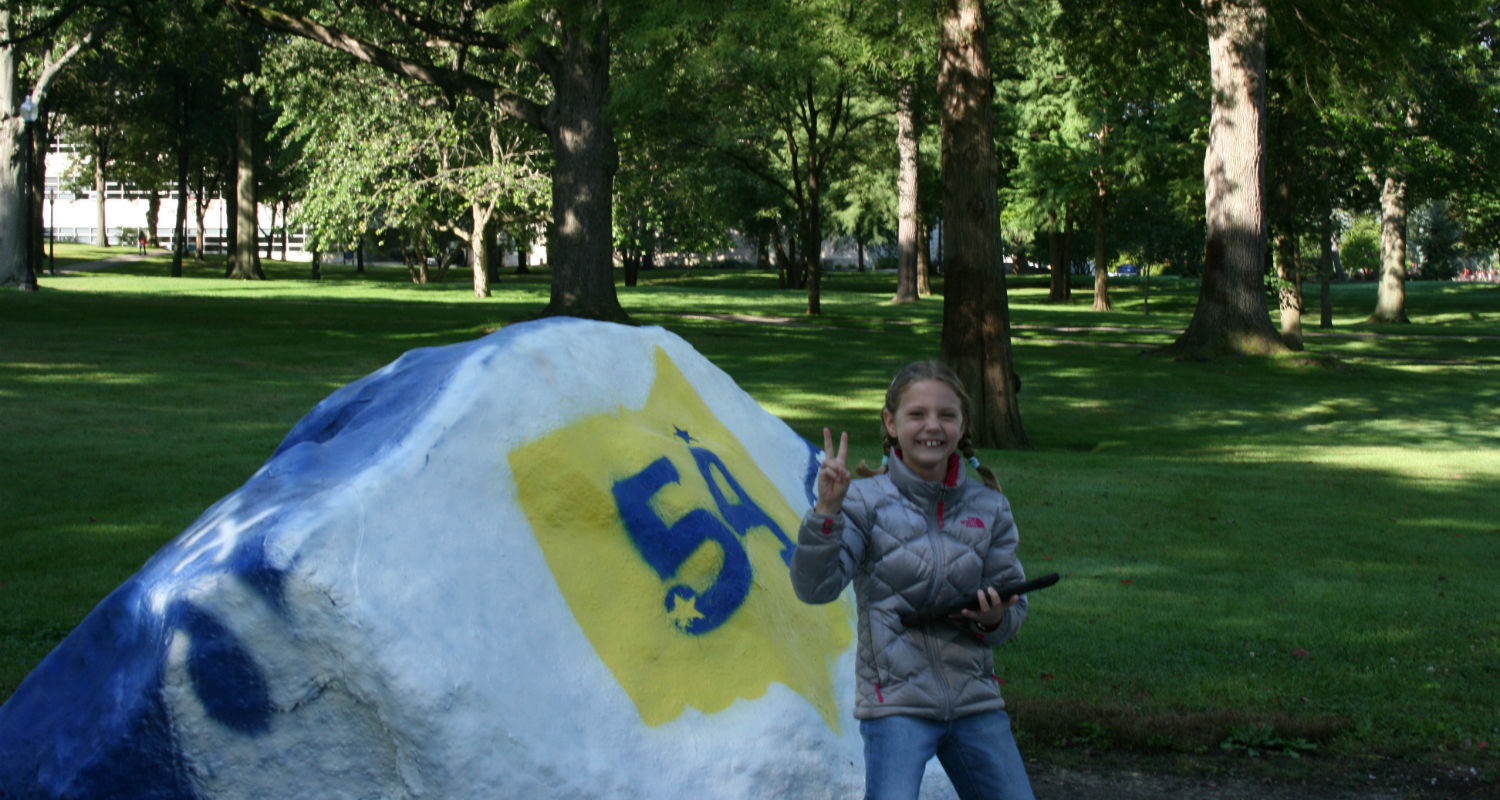A student posing in front of the Kent State Rock in front of campus