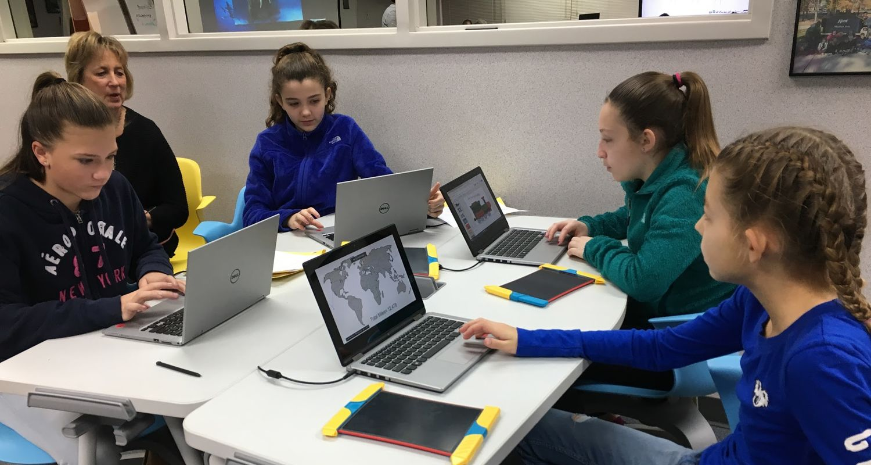Girls and teacher using computers