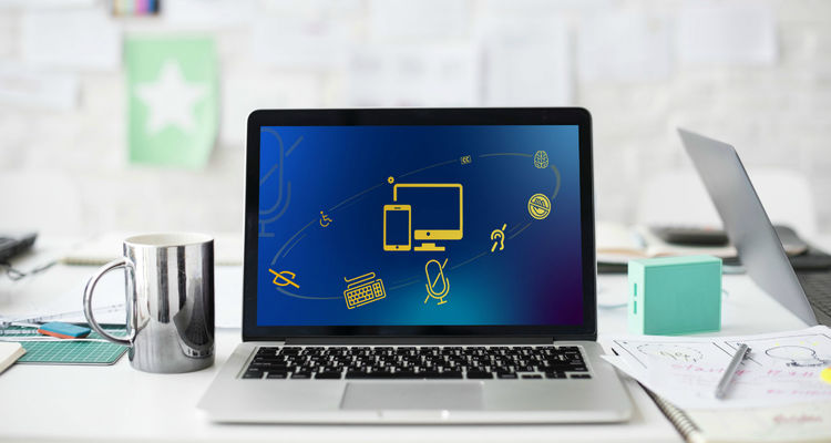 Computer on desk with coffee mug and notebooks