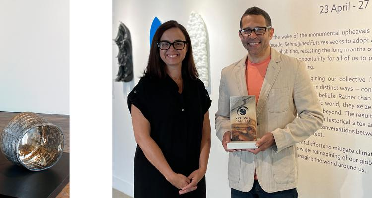Davin Ebanks being presented the top award for the 2nd Cayman Biennial, His work of casted glass baskets are pictured on the left.