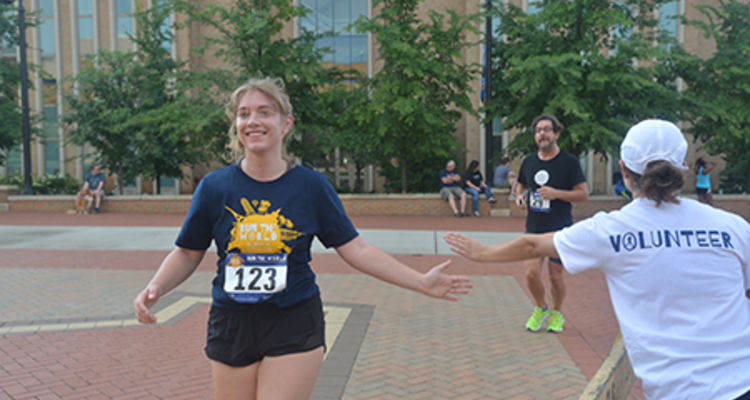 Participants in this year's Run the World 5K receive high-fives from race volunteers.
