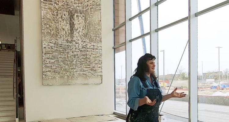 Alumna Diana Al-Hadid speaking in front of her artwork installed at Summa Health Systems