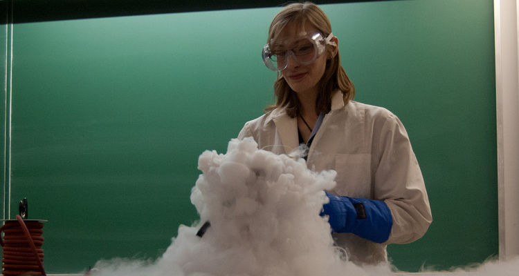 A student performs a chemical demonstration with dry ice.