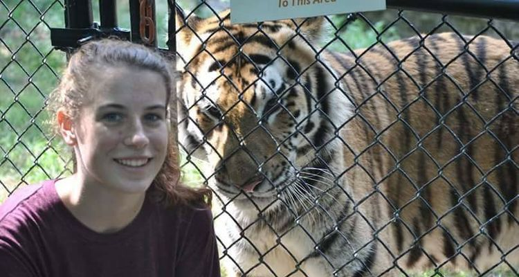 Hirsh posing with Posha, a tiger at the Pittsburgh Zoo and PPG Aquarium, on a day when she was shadowing a zookeeper and learned about tiger husbandry and enrichment.