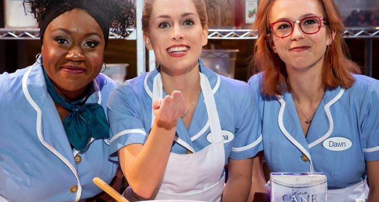 picture of the three leading stars from National Tour of Waitress wearing uniforms behind a table of baking supplies
