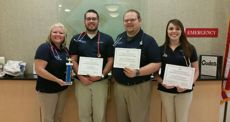 Kent State University at Tuscarawas nursing students display a trophy and certificates that they won at a simualtion competition hosted by the Aultman College of Nursing Sciences and Health.