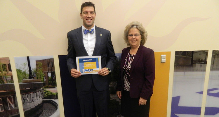 Michael Kavulic from the Office of the President receives a certificate from Kim Hauge, manager for University Wellness and Healthy Campus Promotions. Kavulic won the Destination Chicago grand prize drawing.