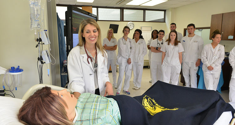 A Kent State nurse educator demonstrates a simulated birth to a class of BSN students