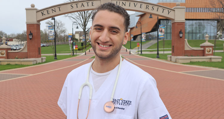 A male nursing student poses in front of the Kent State archway near the Architecture building, near the esplanade extension to downtown Kent