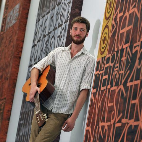 A student musician and music producer poses near a panel of paintings at the Stark Campus.