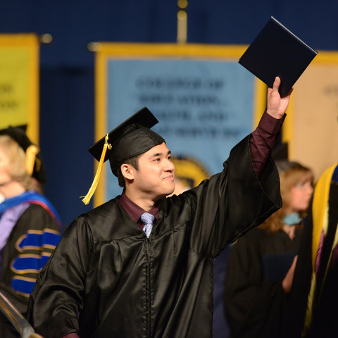 A student in cap and gown holds up his diploma with pride.