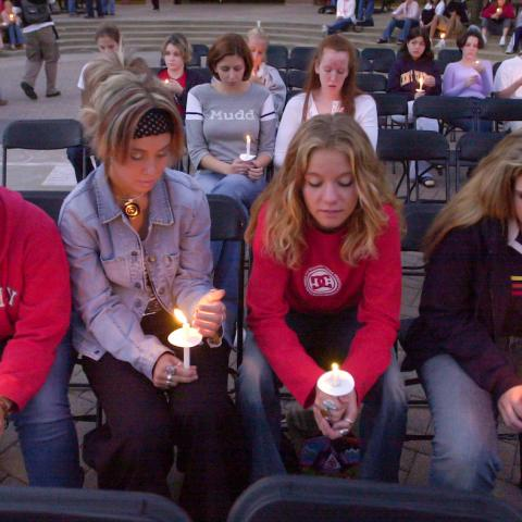 Students sit at a candlelit vigil for the victims of 9/11