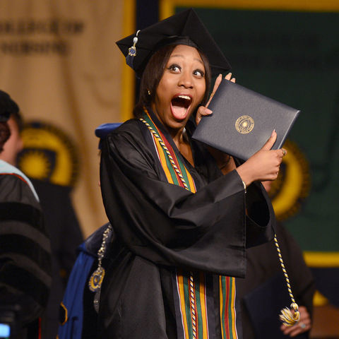 A Kent State graduate from the College of Education, Health and Human Services shows off her degree after walking across the stage during a Commencement ceremony.