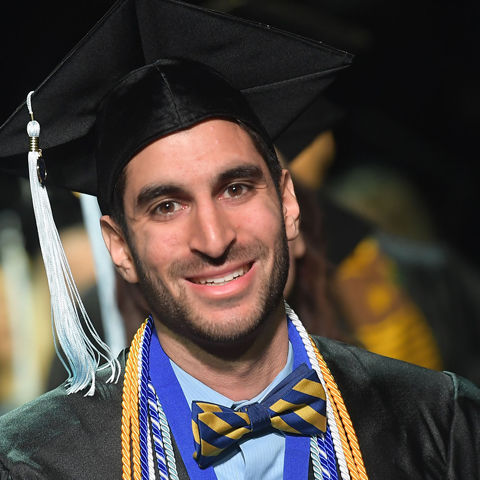 Graduate with cords, cap and gown