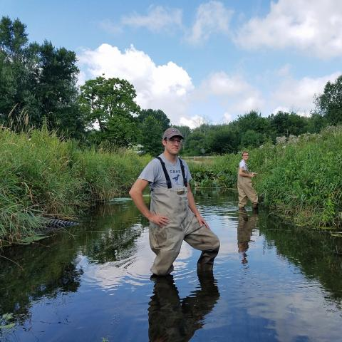 Dave Costello, Ph.D., (left), assistant professor in Kent State University's Department of Biological Sciences in the College of Arts and Sciences, and Devan Mathie (right), an undergraduate honors student, stand in Wahoo Ditch in Ravenna, Ohio.