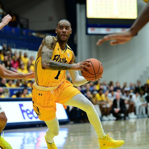 Senior guard CJ Williamson of the Kent State University men's basketball team drives to the basket past a University of Akron player.