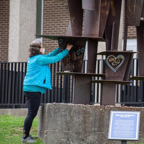 A woman places a flower through the bullet hole left in a sculpture on the Kent State University campus.