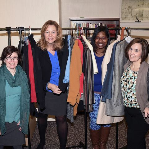 Kent State University employees Tabitha Martin, Lori Bodnar, Alicia Robinson and Kristin Williams stand in the clothes racks at the Kent State Career Closet, located in the lower level of the Williamson House on the university's Kent Campus.