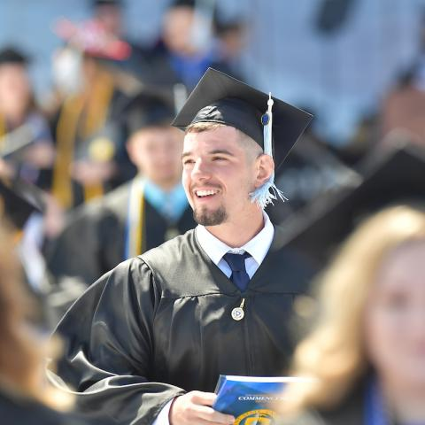 A new Kent State University graduate smiles during the university's spring 2019 commencement ceremony.