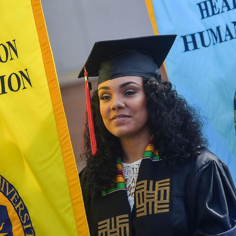A Kent State University graduate, who is serving as a gonfalon bearer, waits to enter Dix Stadium for the university's 2018 One University Commencement.