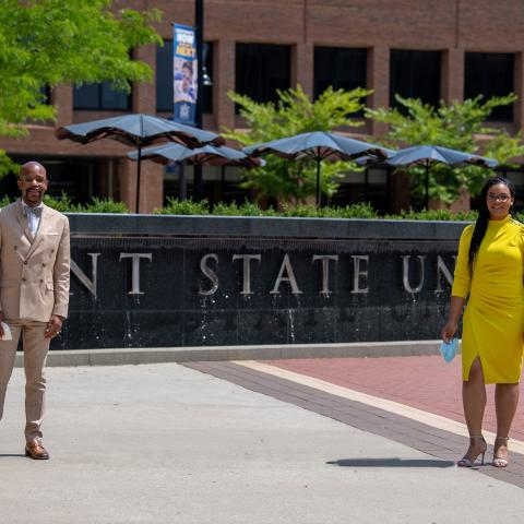 Practicing physical distancing with masks in hand, Lamar R. Hylton, Ph.D., and Taléa R. Drummer-Ferrell, Ph.D., stand in front of the Kent State University fountain.