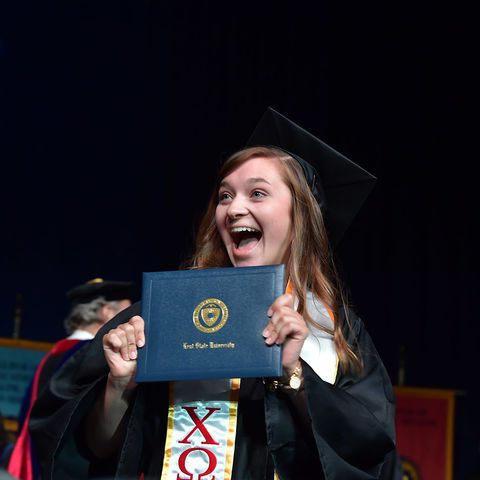 A new Kent State University graduate looks for her family and shows her excitement after receiving her diploma during Summer 2018 Commencement.