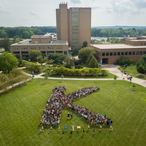 Members of Kent State University's Class of 2023 form a K on campus for a photo with President Todd Diacon, Kent State cheerleaders and the university's mascot, Flash.