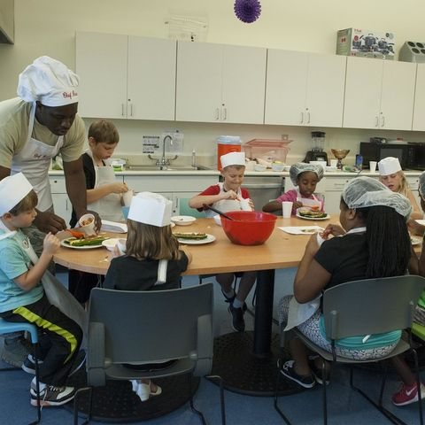 A man in a chef's hat shows young children how to make food.
