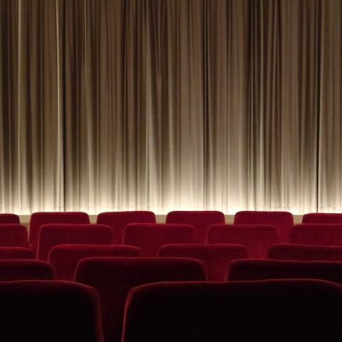 Image of theatre and stage with red seats and a curtain across the stage