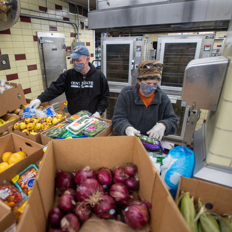 Volunteers Dave and Terri Cardy pack and weigh produce to hand out at the Campus Kitchen in Beall Hall. The food is mostly donated by Trader Joe's locations in the Cleveland area.
