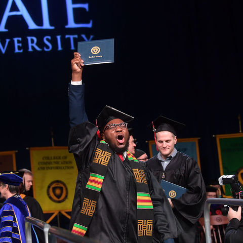 A Kent State graduate celebrates as he crosses the stage during his Commencement ceremony.