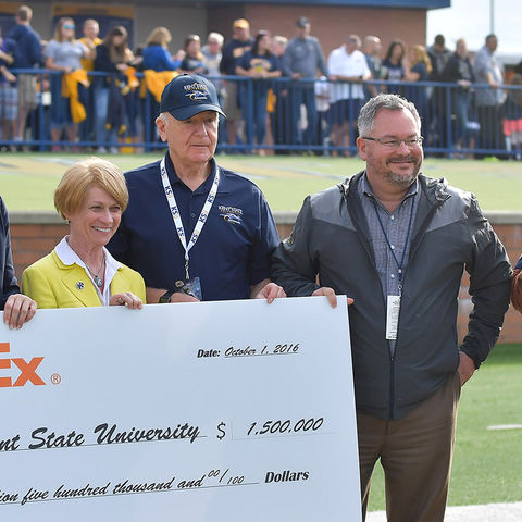 Virginia Albanese (far left) of FedEx Custom Critical presents a giant check to Kent State President Beverly Warren. Also pictured are Interim Dean Robert Sines, Vice President Stephen Sokany and Flash.