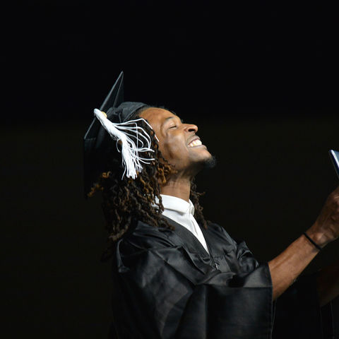 A new Kent State graduate holds his diploma up in victory after he walked across the stage during the Fall 2015 Commencement ceremony.