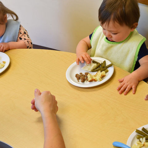 A woman sits at a table with small children eating healthy food.