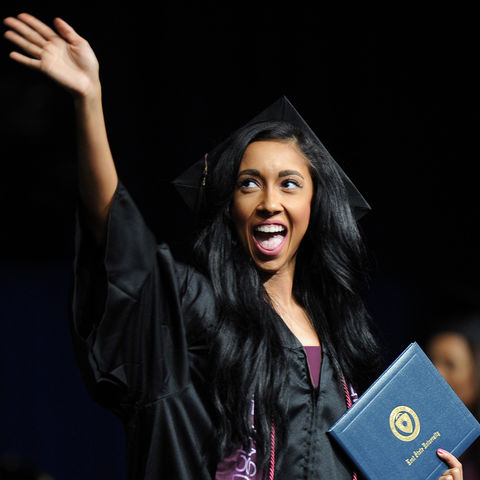 A graduate at the Summer 2016 Commencement ceremony waves to her family after receiving her diploma.