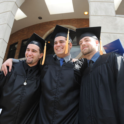 Three friends celebrate their graduation from Kent State following the morning commencement ceremony.