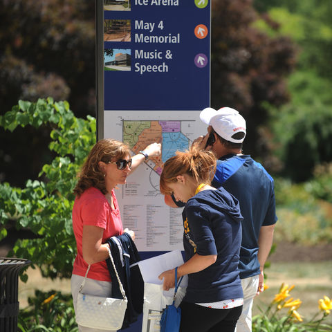 A family navigates their way through central campus using signage in the Beyer-Murin Gardens by the Library.