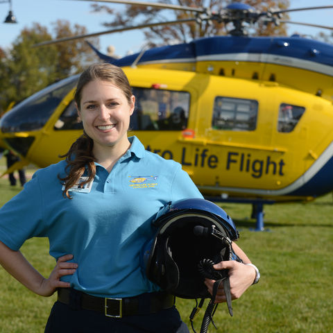 A master's student in the nursing program poses in front of a Metro Life Flight helicopter that landed on the esplanade extension. The student is part of a program that gives them experience as flight nurses on the helicopters.