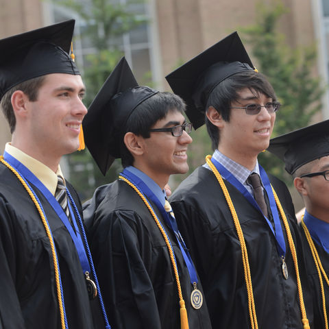 Four friends pose for a photo after the summer 2013 Commencement near the fountain in the Risman Plaza.