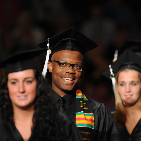 A summer 2014 Kent State graduate smiles as he walks down the aisle during commencement.